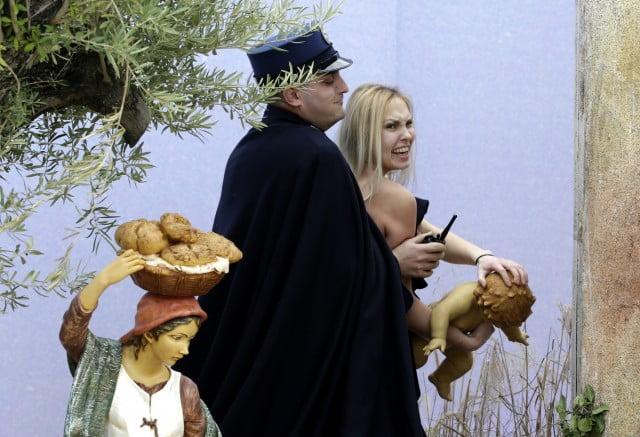 VIDEO: Activista de Femen desnuda se roba a el niño Jesus del pleno pesebre Vaticano